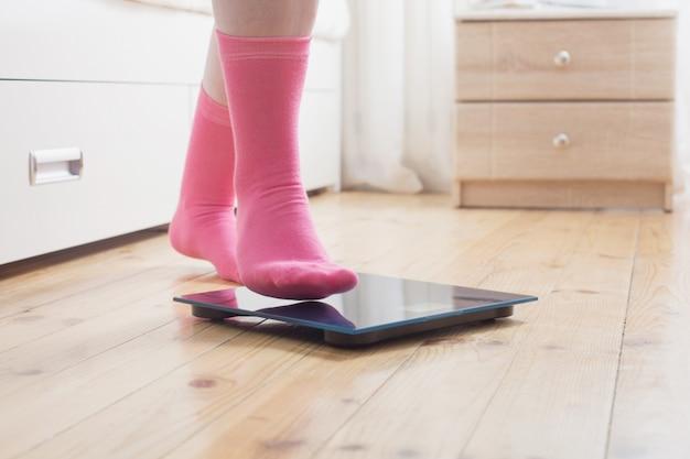 Pés femininos em meias nas balanças de chão