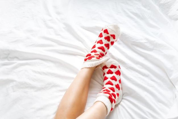 Pés femininos em meias quentes com corações vermelhos em uma cama branca
