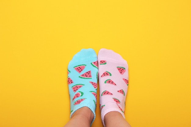 Pés femininos em meias rosa e azuis em melancia impressão sobre um fundo amarelo pastel. vista superior. copie o espaço.