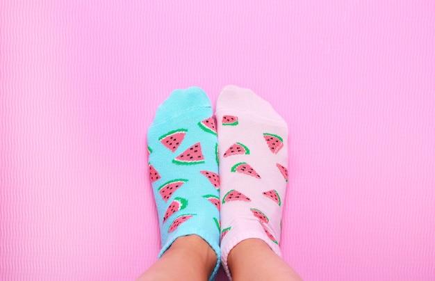 Pés femininos em meias rosa e azuis em melancia impressão sobre um fundo rosa pastel. vista superior. copie o espaço.
