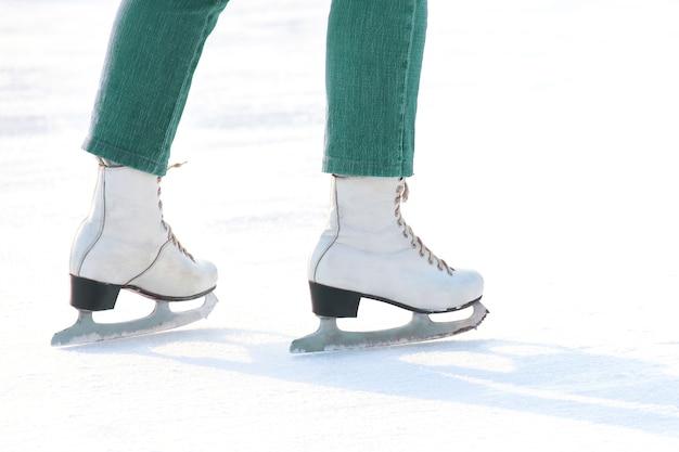 Pés femininos em patinação no gelo branco na pista de gelo. esportes, hobbies e recreação de pessoas ativas