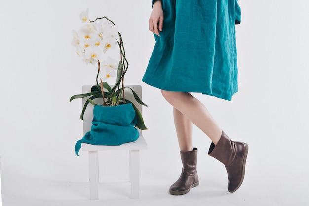 Pés femininos em roupas de linho e sapatos ao lado de uma flor em um fundo branco
