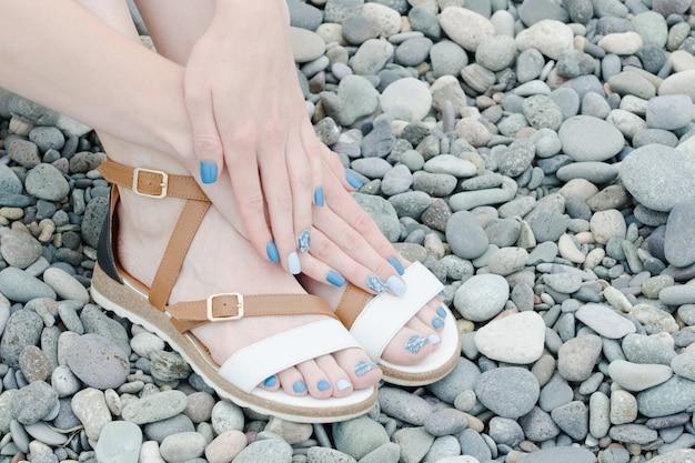 Pés femininos em sandálias e mãos com uma manicure azul em seixos
