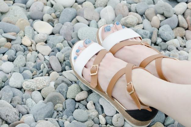 Pés femininos em sandálias