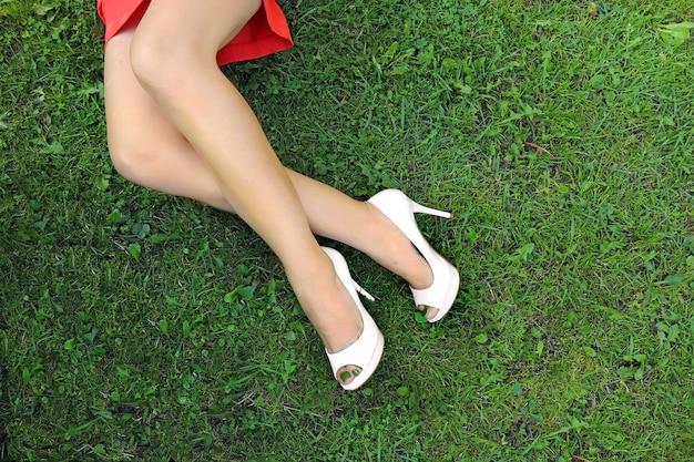 Pés femininos em sapatos brancos na grama verde