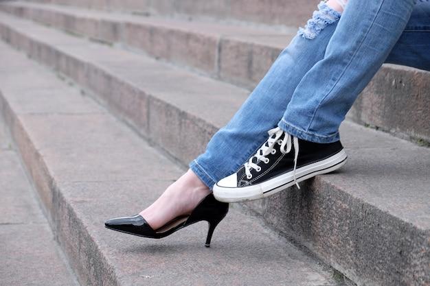 Pés femininos em sapatos diferentes em escadas de pedra