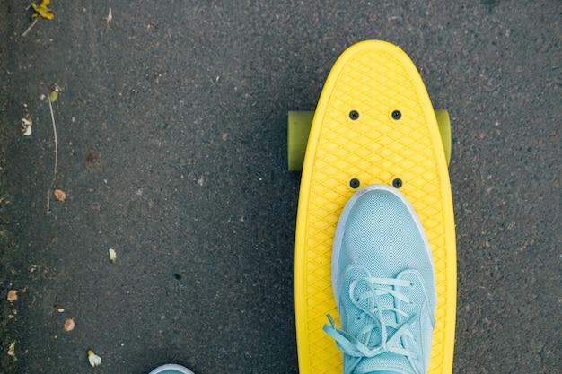 Pés femininos em tênis azuis em um skate amarelo com rodas verdes andando na estrada