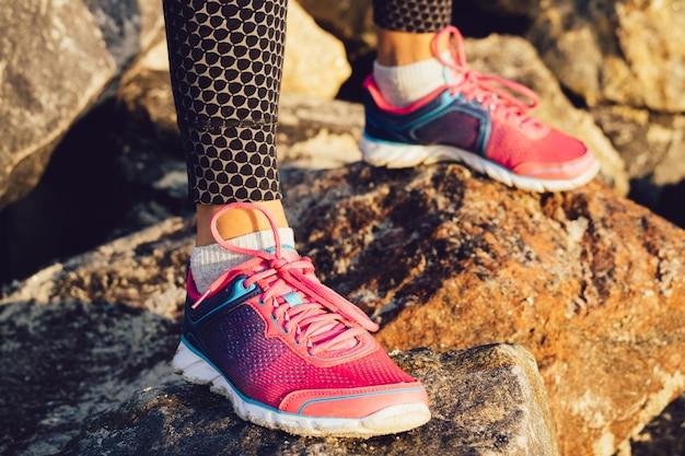 Pés femininos em tênis rosa e azuis em pé sobre as pedras rochosas no sol da manhã