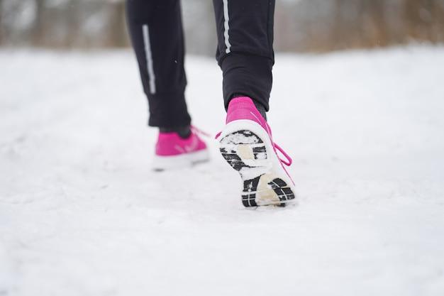 Pés femininos em tênis rosa enquanto jogging na floresta de inverno.