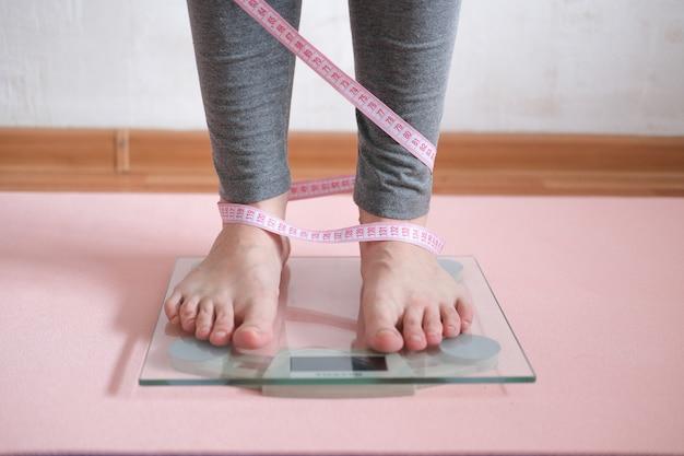Pés femininos na balança com a medição do peso corporal.