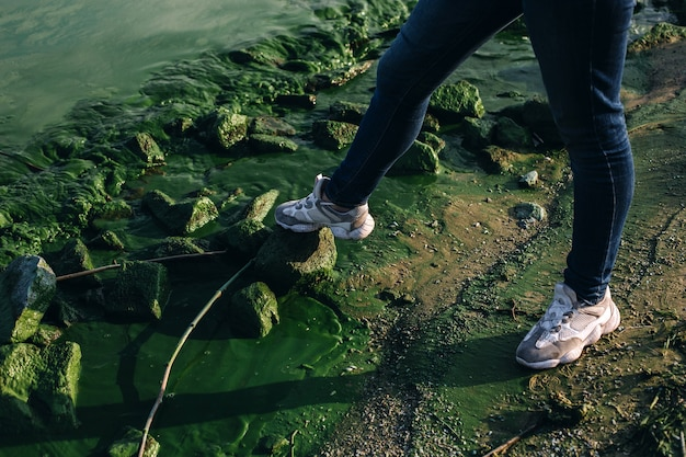 Pés femininos na margem do rio com pedras cobertas de musgo e água suja com algas