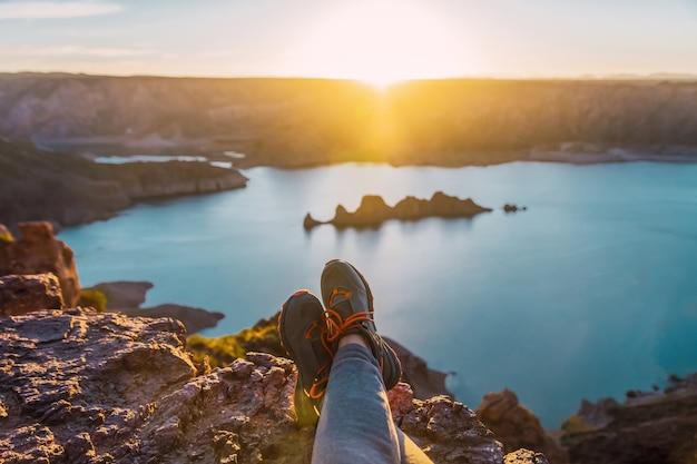 Pés femininos na montanha. mulher feliz apreciando a vista do lago ao pôr do sol