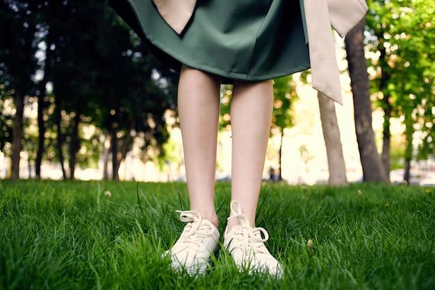 Pés femininos no gramado caminham no parque ao ar livre