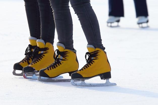 Pés femininos patinando na pista de gelo. esporte e entretenimento. descanso e férias de inverno.