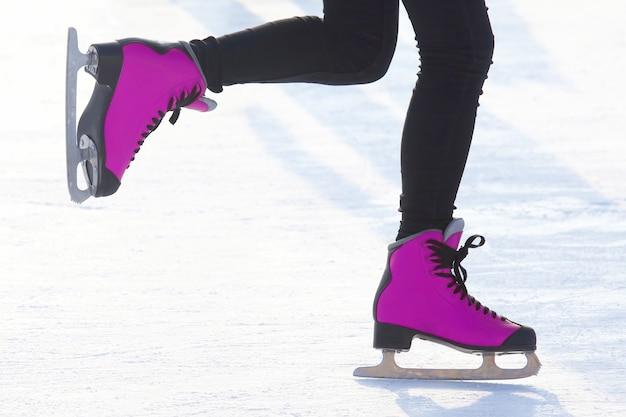 Pés femininos patinando na pista de gelo. hobbies e recreação. esportes e feriados