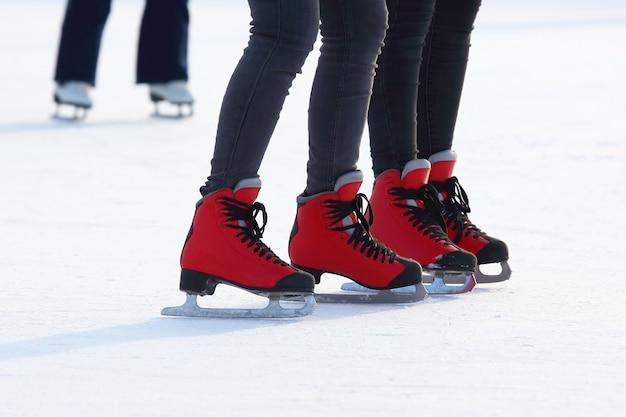 Pés femininos patinando na pista de gelo