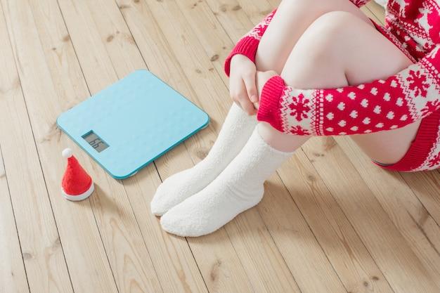 Pés femininos perto de balanças eletrônicas azuis para controle de peso com chapéu de papai noel de natal no chão de madeira