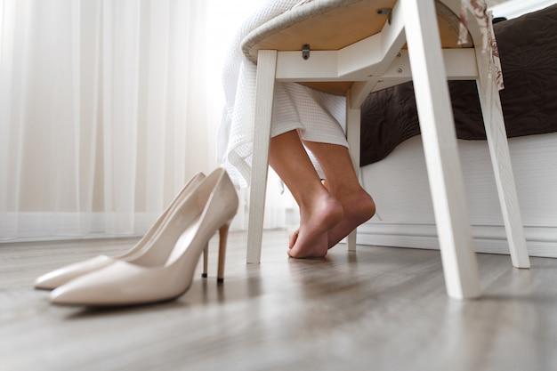 Pés femininos perto dos sapatos, sapatos femininos bege de salto alto no chão