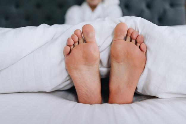 Pés femininos saindo de um cobertor