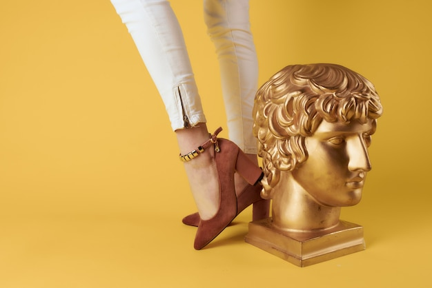 Pés femininos sapatos da moda estilo elegante cabeça escultura fundo amarelo