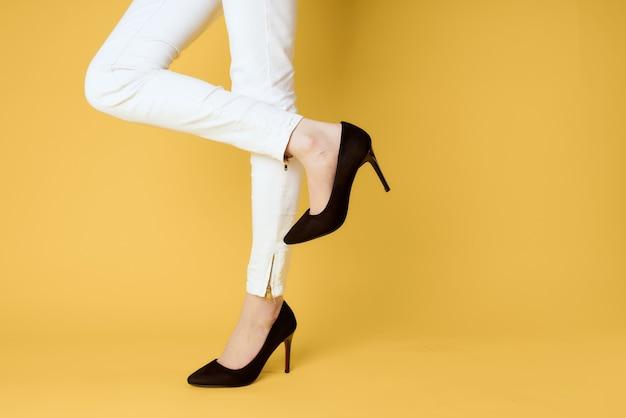 Pés femininos sapatos pretos moda roupas estúdio amarelo.
