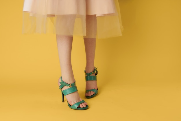 Pés femininos sapatos verdes estilo elegante sapatos modernos fundo amarelo