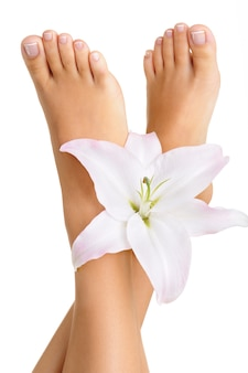 Pés femininos saudáveis e elegantes, bem tratados com flores em um