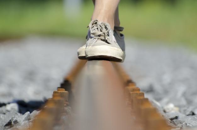 Pés femininos se equilibrando em trilhos de trem