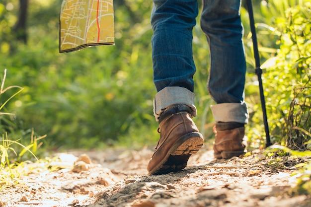 Pés homem caminhadas ao ar livre e floresta em fundo