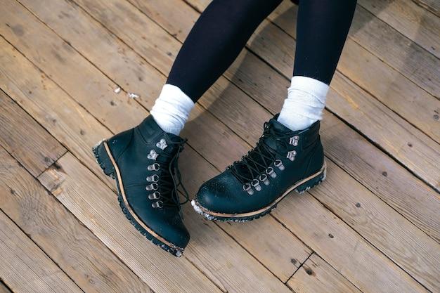 Pés irreconhecíveis de mulher jovem com meias brancas de cano alto e botas pretas. menina andando na cidade.