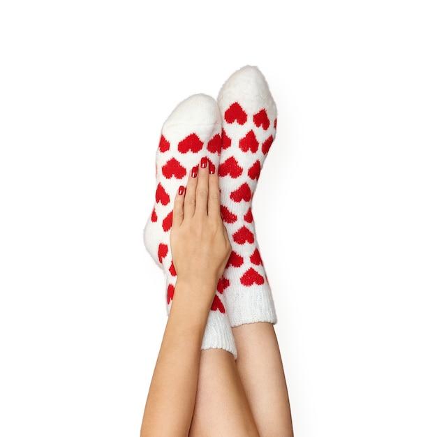 Pés lindos em meias quentes com estampa de corações isolados.