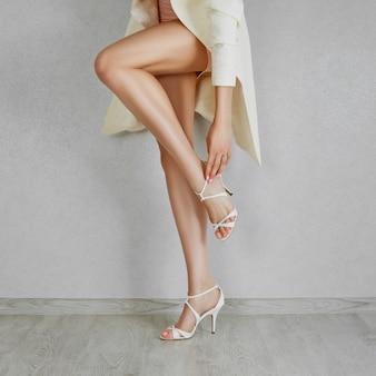 Pés longos da mulher desencapada em sandálias do bege do salto alto. feche de sapatos de fixação.