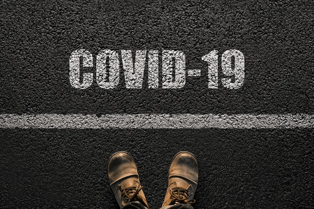 Pés masculinos com botas no asfalto com o texto covid-19. conceito de humanidade e vírus. coronavírus e viagens