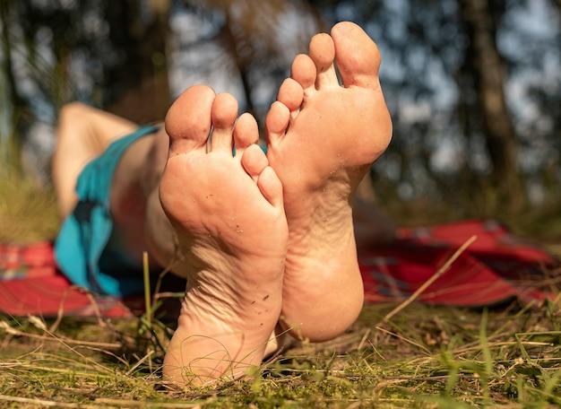 Pés masculinos com salto na grama no verão ensolarado close-up