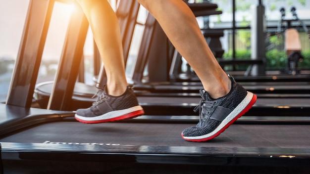 Pés masculinos de tênis correndo na esteira na academia. conceito de exercício.