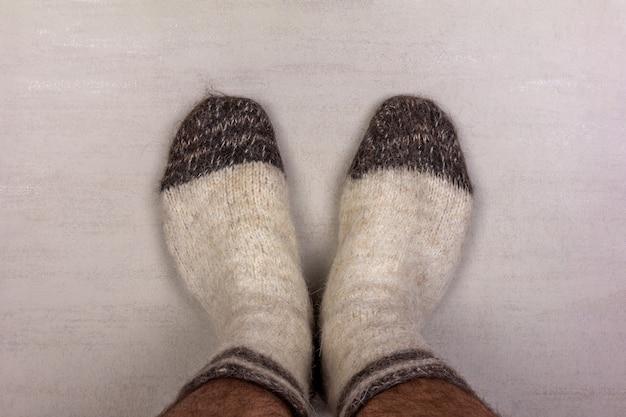 Pés masculinos em meias brancas de malha de lã