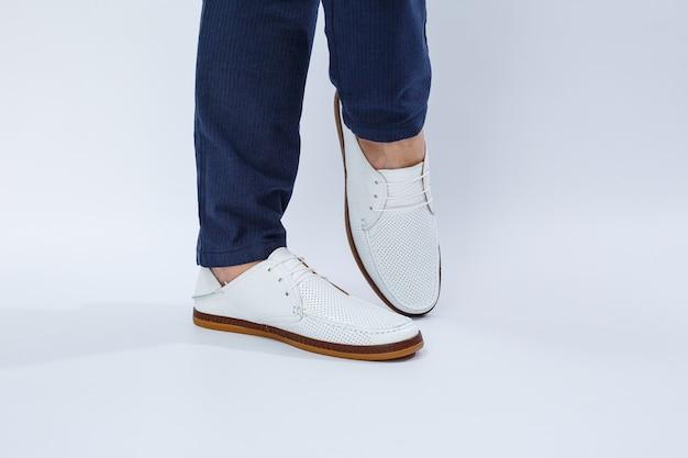 Pés masculinos em tênis branco do dia a dia feitos de couro natural com cordão. foto de alta qualidade