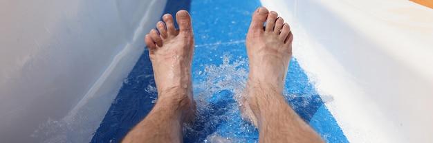 Pés masculinos no fundo da montanha-russa no parque aquático closeup