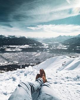 Pés masculinos, sentado em um penhasco coberto de neve sob o lindo céu nublado