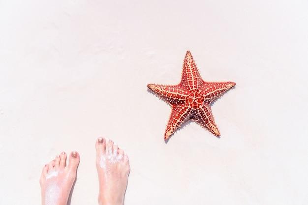 Pés na areia branca tropical com estrela do mar vermelha