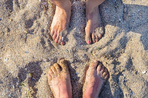 Pés na areia de uma praia, verão relaxe férias