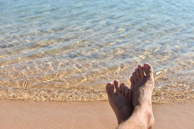 Pés na areia na praia contra um mar azul