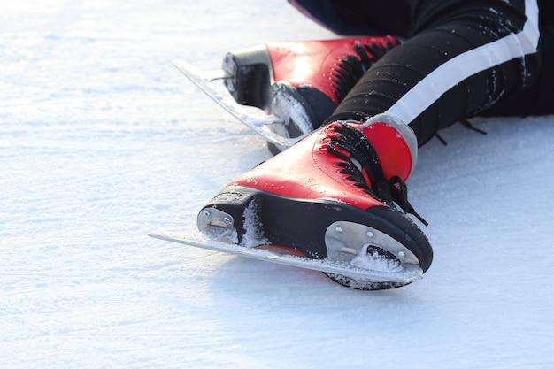 Pés nos patins de um homem caído em uma pista de gelo