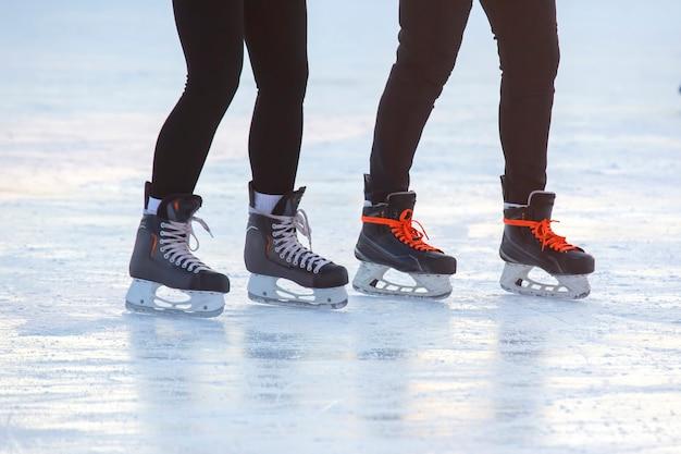 Pés nos patins de uma pessoa rolando na pista de gelo. hobbies e esportes