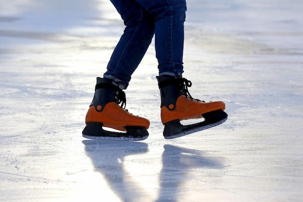 Pés nos patins de uma pessoa rolando na pista de gelo