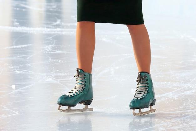 Pés patinando menina patinando na pista de gelo. esportes, hobbies e recreação de pessoas ativas