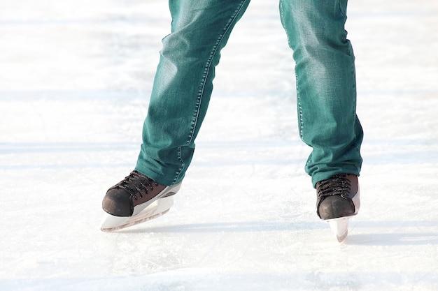 Pés patinando na pista de gelo. esporte e entretenimento. descanso e férias de inverno.