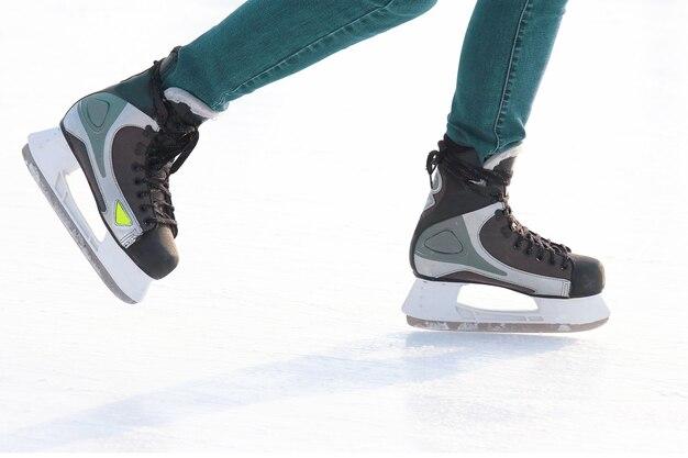 Pés patinando na pista de gelo. hobbies e recreação. esportes e feriados