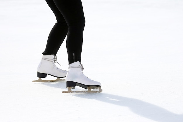 Pés patinando na pista de gelo