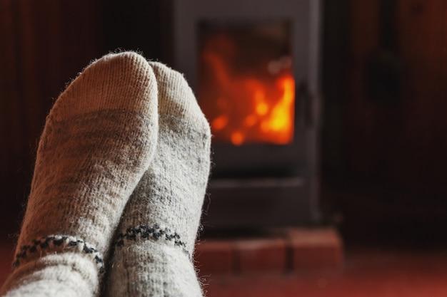 Pés pernas em roupas de inverno meias de lã na lareira em casa no inverno ou no outono à noite relaxando e se aquecendo